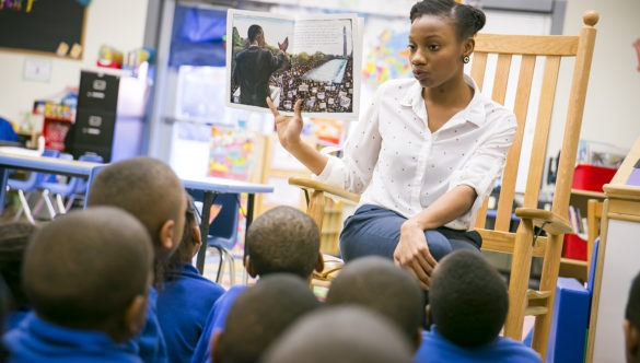 A City Year alumni reading a book to young students sitting on the floor
