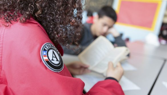 An AmeriCorps member and a student read a chapter book together.