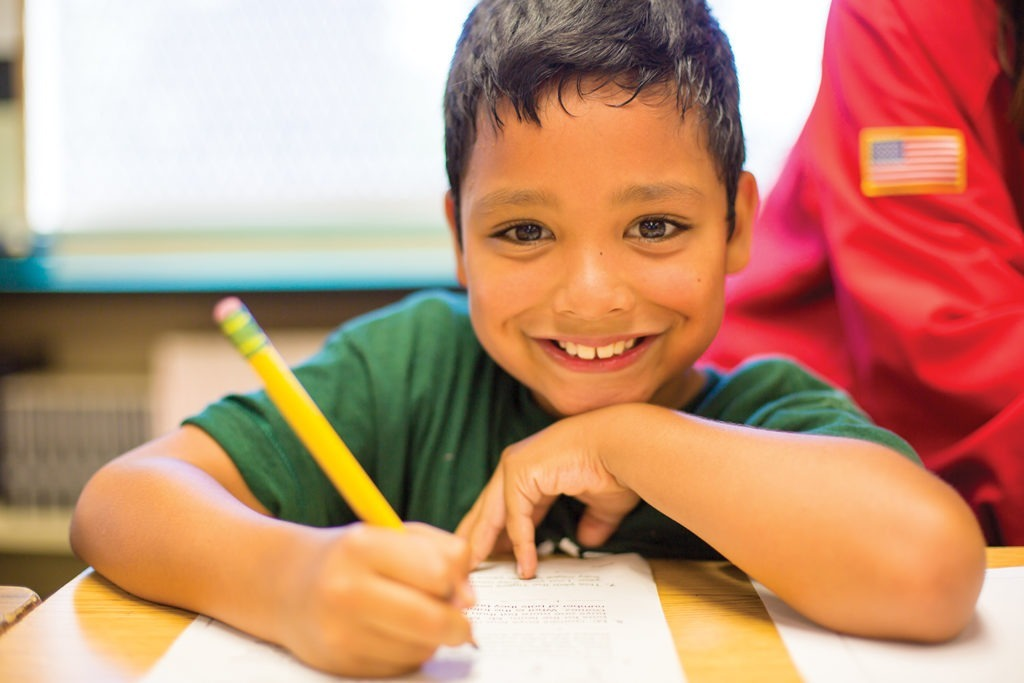 smiling elementary student doing worksheet at a desk