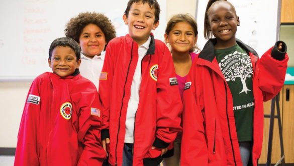 Group of elementary students smile while wearing their AmeriCorps members' jackets