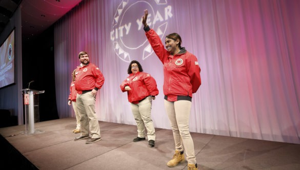 An AmeriCorps member raises her hand on stage at a City Year event