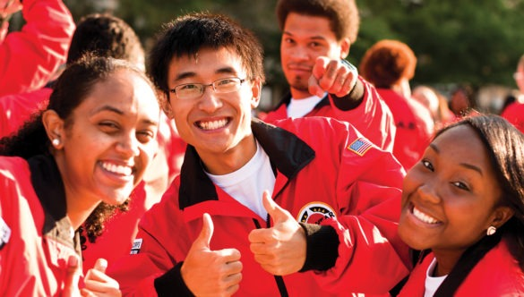 A group of AmeriCorps members smile with their thumbs up.