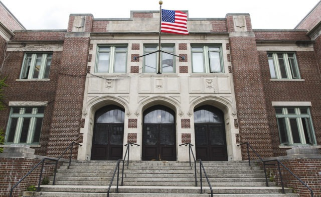 The entrance to a school with an American flag flying in the front.