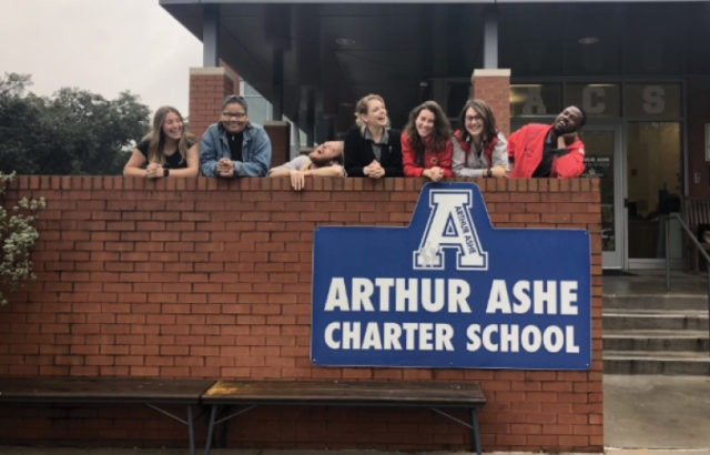 A team of seven AmeriCorps members lean over a brick wall smiling at the Arthur Ashe Charter school
