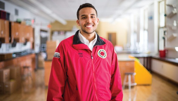 AmeriCorps member stands and smiles in the front of a school science lab.