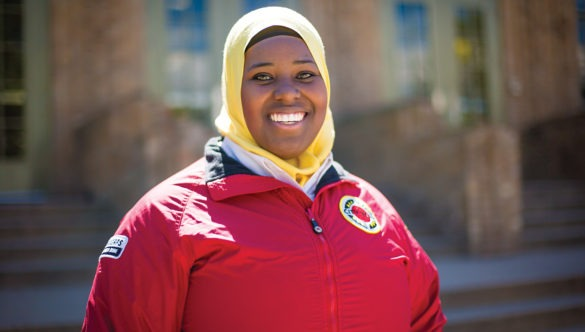 AmeriCorps member stands in by the front steps on a school building and smiles..