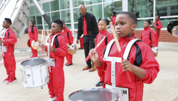 An elementary school marching band drums, dressed in red