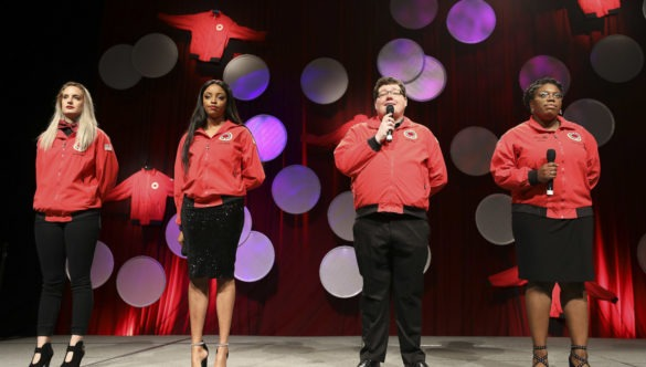 4 AmeriCorps members stand on stage together at a City Year event