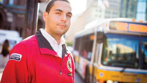 AmeriCorps member stands at a bus stop.