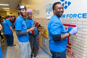 Three volunteers pause from painting college logos on an interior school wall to smile for the camera