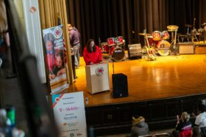 AmeriCorps member Jenny Roberts speaks from a podium on stage in an auditorium