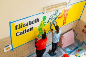 Two volunteers paint a mural of three children playing soccer together in a school stairwell
