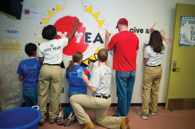 A group of AmeriCorps members and volunteers work on painting a school mural.