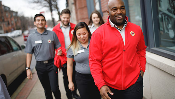 A group of AmeriCorps members and staff walk in a group on the side walk and share a laugh.