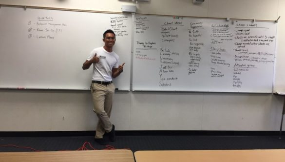 Paolo Aligada gives double thumbs-up while standing in front of a whiteboard covered in lesson plan strategies.