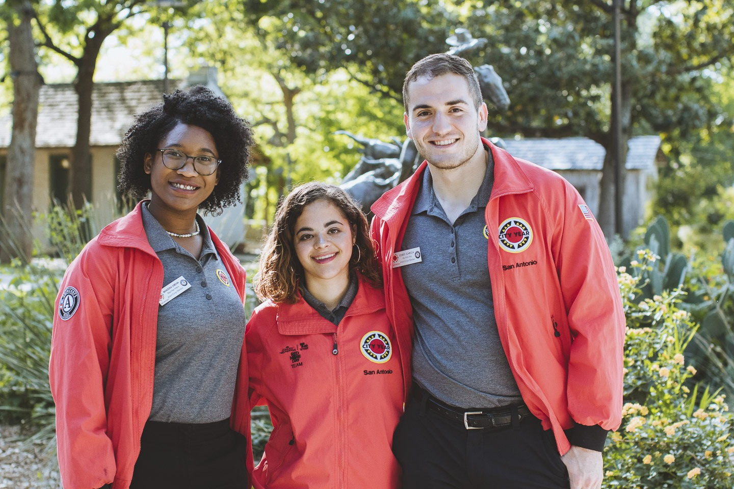 3 AmeriCorps members smile at the camera wearing their red City Year jackets