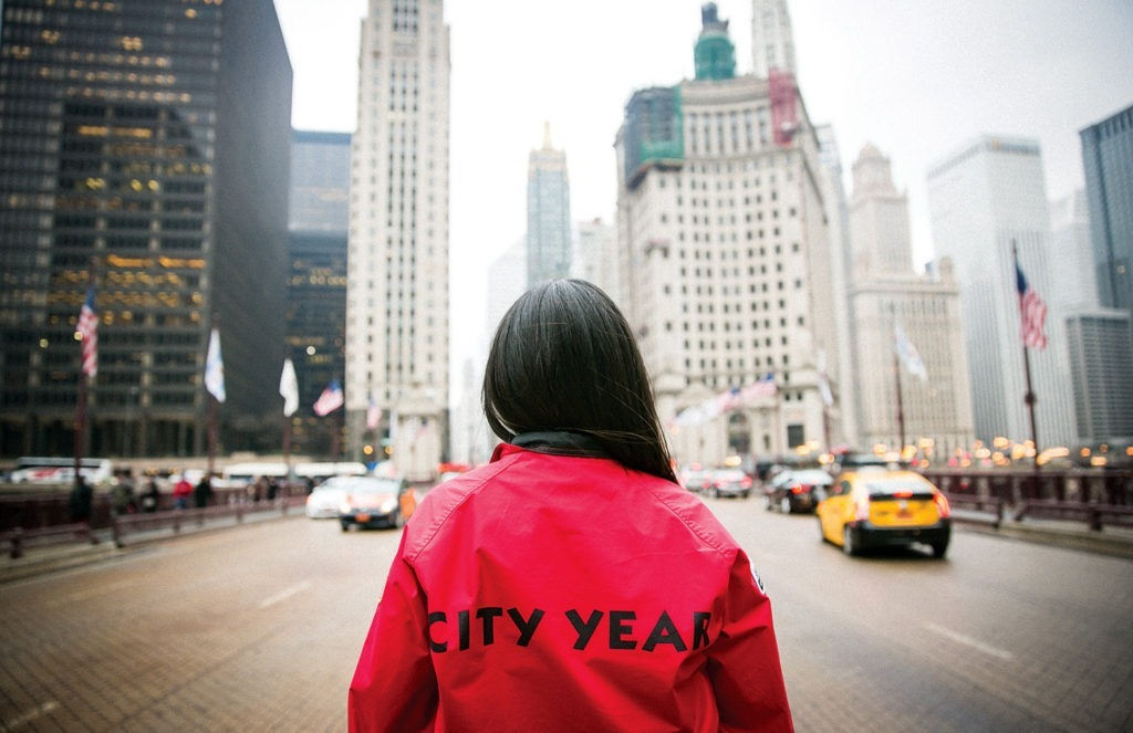 AmeriCorps member stands on a busy street looking up at the city.