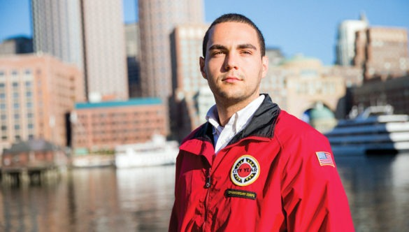 AmeriCorps member stands in front of the city skyline and water.
