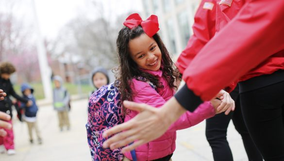An elementary school student wearing a bow and a backpack high-fives several AmeriCorps members as she arrives at school on time