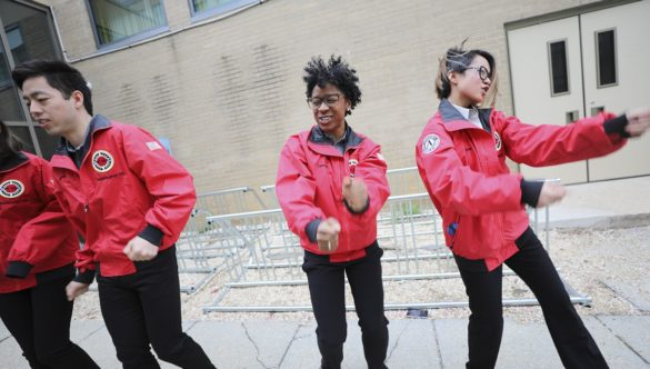 Four AmeriCorps members dance as they try to energize students for a day of learning