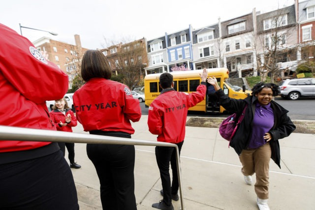 As students exit the school bus they find a team of City Year AmeriCorps members lined up to welcome them to school