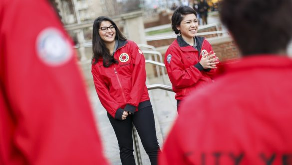 Two AmeriCorps members and their teammates stand outside a school, ready to greet students as they arrive
