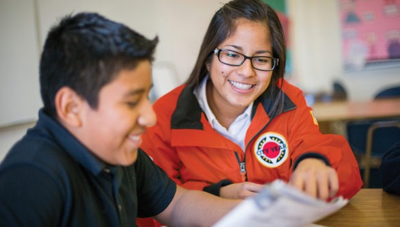 city year americorps member with a student sitting at a desk as they read together from the same paper