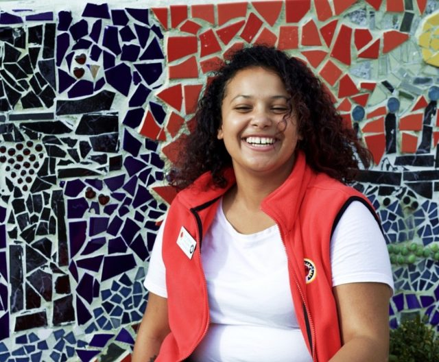City Year AmeriCorps member smiling in front of a mosaic wall