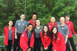 A team picure of ten AmeriCorps members in front of trees