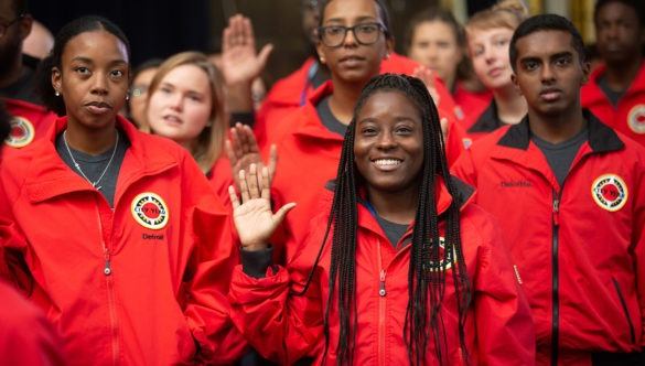 A cohort of City Year AmeriCorps members raise their right hand as they say the City Year pledge