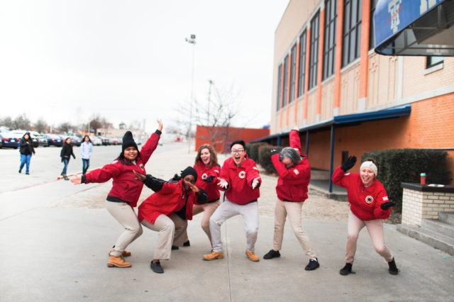Six AmeriCorps members strike an energetic pose in front of a school