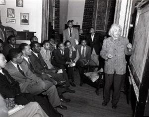 Albert Einstein stands at a chalkboard. A class of African-American men watch him lecture.