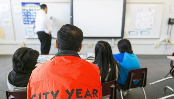 A city year americorps member looks on from the back of a classroom as a teacher writes on a board and students look on