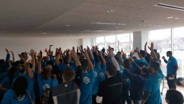 AT&T volunteers throw their hands up in a spirit break at the end of their service day