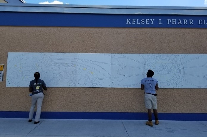 Team Care Force traced a mural in preparation for the service day