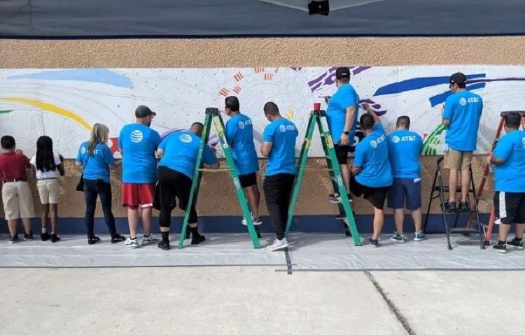 AT&T volunteers and students from the school paint the plywood mural.