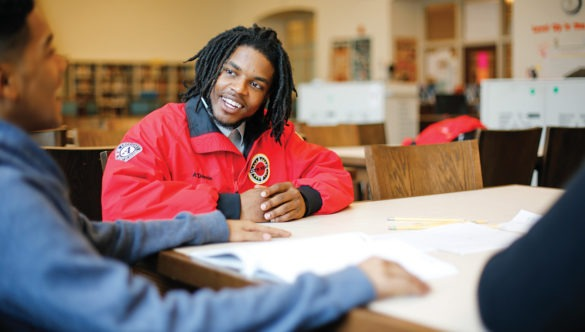 an americorps member sits at a table smiling at a student