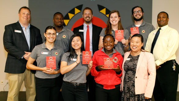 AmeriCorps members pose with their graduation awards with City Year staff
