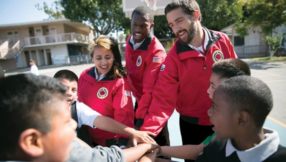 americorps members place their hands in a spirit break with students