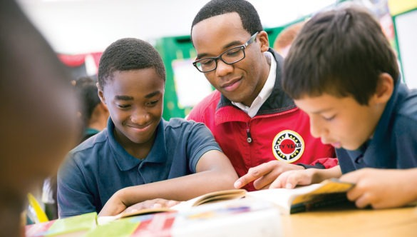 a middle school student smiles while reading with an AmeriCorps member