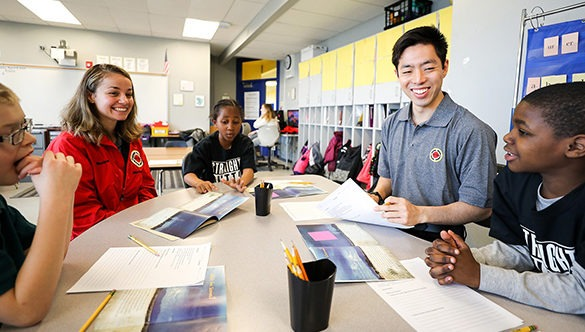 City Year AmeriCorp Members tutoring students around a work table