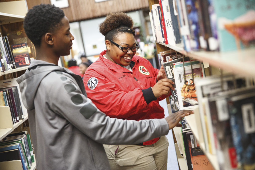 City Year AmeriCorps member in library with student