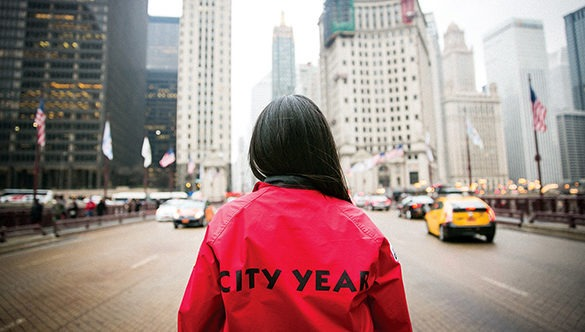 City Year AmeriCorp Member with their back towards the camera facing a large cityscape