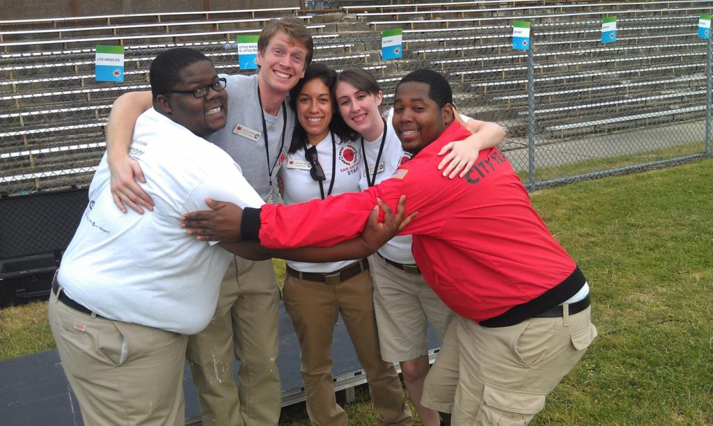 City Year Columbus alum Alen Amimi stands in a group hug with his teammates
