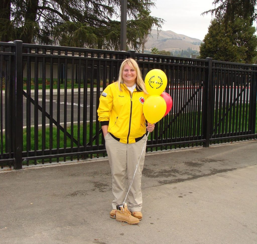 Megan Baker, City Year LA alum, stands in her yellow jacket holding balloons