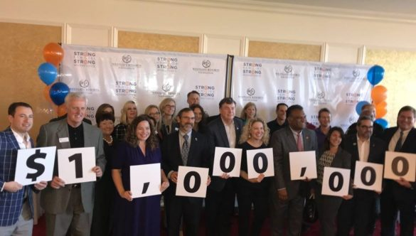 Westgate employees hold a sign that says $1,000,000 to signify this milestone