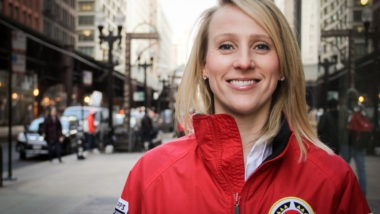 Emily Kean, former Senior Director of Impact Operations at City Year Chicago, in the iconic red jacket posing outside the office in Chicago, Illinois.