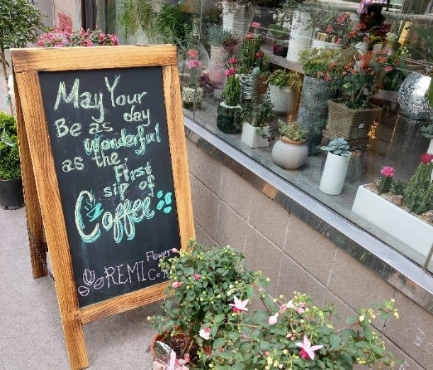 "A chalkboard sign with the words ""May your day be as wonderful as the first sip of coffee"" sits next to a ledge covered with various types of plants."