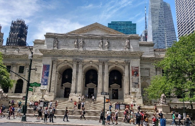 New York Public Library with people walking around the sidewalk in front.