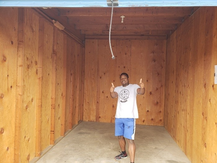 Senior AmeriCorps Member Mark Johnson stands proudly in the Storage Unit he has just emptied.